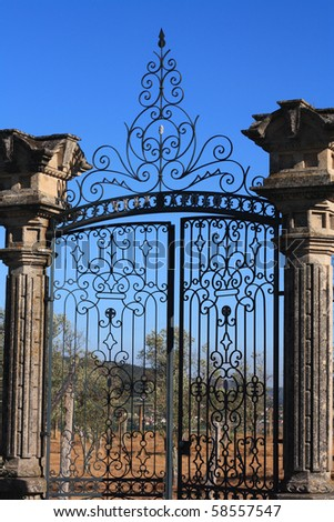 old wrought iron gates mounted on two granite columns