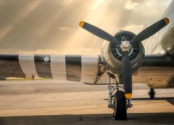 Old WW2 Dakota twin engine Operation Overlord aeroplane parked with sun setting over plane wings sunlight rays from sky. Wheel chocks and three propellers ready for takeoff.