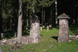Old WWI german and russian soldier military cemetery near Auce Latvia with stone gate and crosses