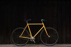 Old yellow bike against dark wood wall. Yellow singlespeed bike. Yellow single speed Favorite bike.