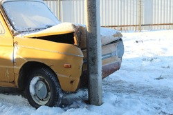 old yellow car collided with a pillar in winter