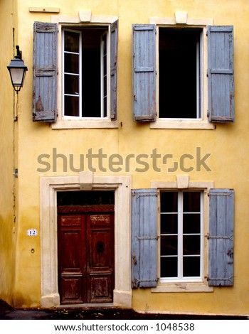 Old Yellow House With Three Windows With Blue Shutters, A Door And ...