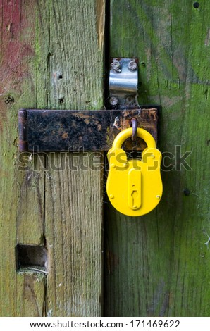 old yellow padlock on the door closed