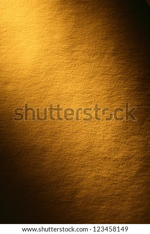 Old yellow paper surface with beam of light. Good background for your text