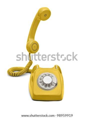 Old yellow rotary phone hook and ready to talk