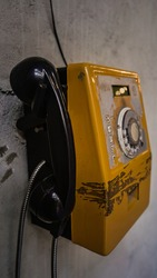 Old Yellow Vintage and Grungy Phone hanged on a grungy wall