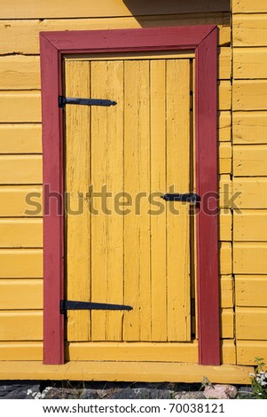 Old yellow wooden door with red architrave #70038121