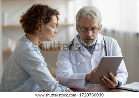Older adult doctor consulting young female patient using digital tablet tech during checkup appointment meeting. Woman client visiting physician listening diagnosis treatment prescription in hospital.