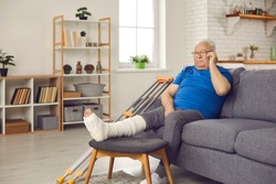 Older adult with physical injury at home: Sad senior man with broken leg in plaster cast sitting on sofa and making phone call on mobile to talk to doctor about bone fracture or share news with family
