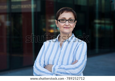 Older business woman headshot. Close-up portrait of executive, teacher, principal, CEO. Confident and successful middle aged woman 40 50 years old wearing glasses and shirt. ストックフォト ©