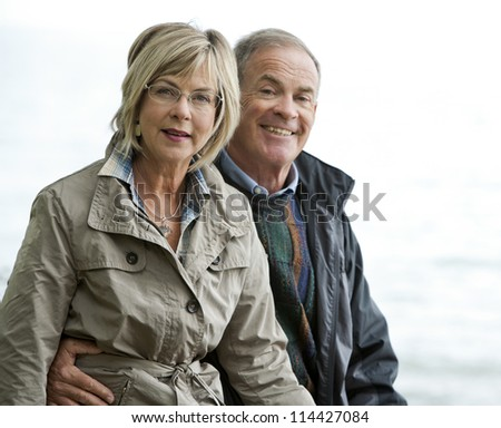 older casual couple sitting in the grass outdoors