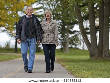 older casual couple walking in the park outdoors