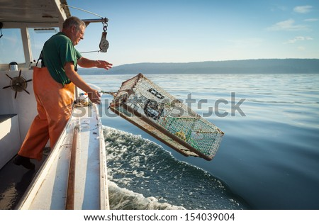 older, caucasian Man in overalls standing on boat throwing lobster trap into water, Maine, USA