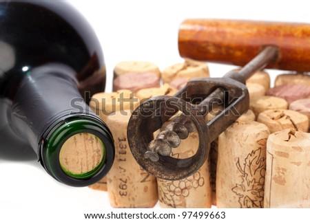 Older corkscrew lies on some corks beside a wine bottle