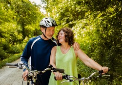 Older couple bicyclists talking and smiling at each with their bicycles; lush summer foliage in background