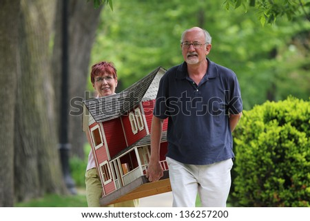 Older couple carrying a suburban home in residential neighborhood