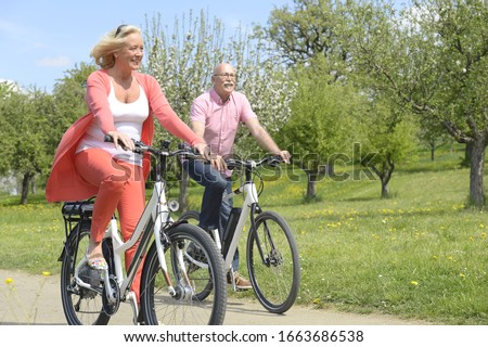 Older couple cycling through countryside