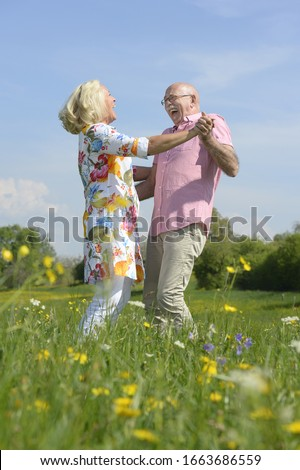 Older couple dancing together in meadow