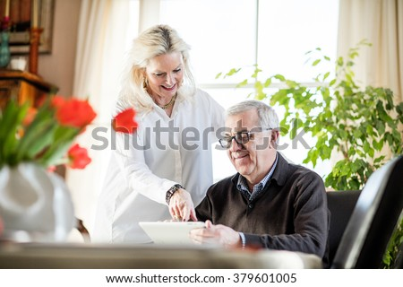 Older couple having fun and smiling while working from home on notebook with green flowers and window light around them