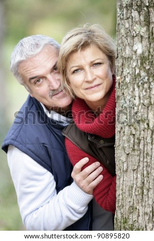 Older couple peeking around a tree