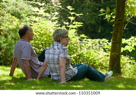 Older couple sitting in the grass - stock photo