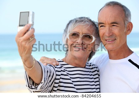 Older couple taking their own photograph at the beach