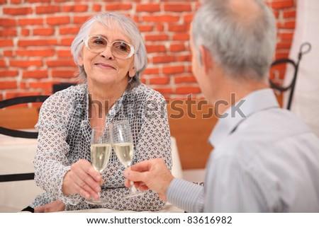 older couple toasting at restaurant - stock photo