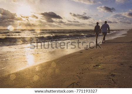 Older couple walks on the beach holding hands at sunset just as a wave retreats from the shore.