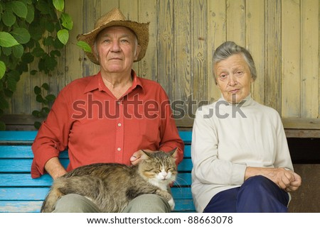 Older couple with cat sit outdoors