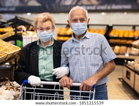 older european couple wearing mask and gloves with covid protection chooses buns and bread in supermarket bakery ストックフォト ©