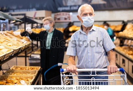 older european man wearing mask and gloves with covid protection chooses buns and bread in supermarket bakery ストックフォト ©