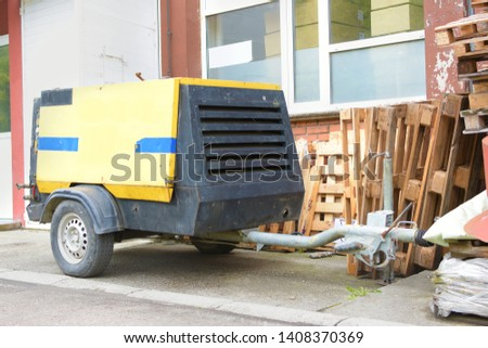 Older generation portable powerhouse or portable compressor with generator next to a pile of wooden pallets. #1408370369