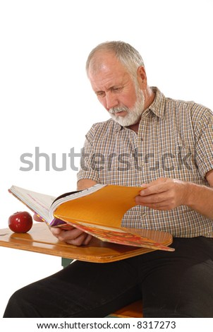 Older gentleman back in school at a desk with a textbook