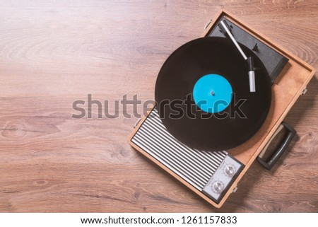 Older Gramophone with a vinyl record on wooden table, top view and copy space,photo. #1261157833