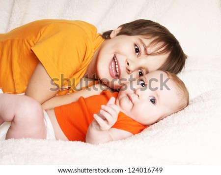 Older happy laughing brother holding cute baby sister lying on fur blanket, studio shot