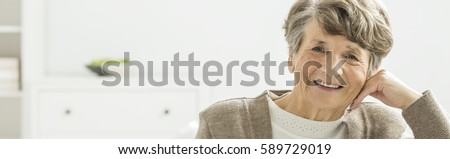 Older happy woman spending afternoon in nursing home