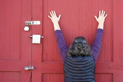 Older Italian woman with hands up on a red wall with doors and silver locks and wearing a purple shirt and black puffy vest like she's being arrested