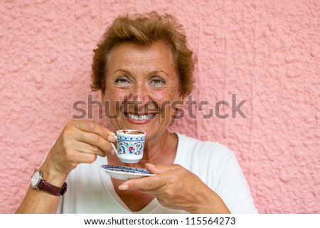 Older Lady drinking her Turkish coffee infront of pink  textured wall