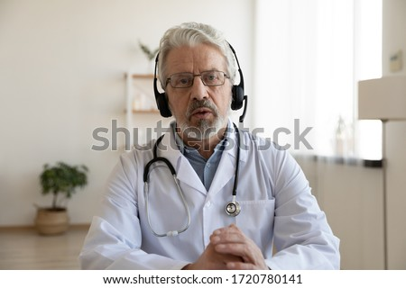 Older male doctor therapist wearing headset videoconferencing talking to web camera consulting virtual patient online by video conference call chat. Telemedicine, telehealth concept. Webcam view.