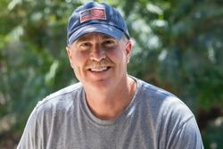 Older male smiles warmly outside wearing USA flag baseball hat