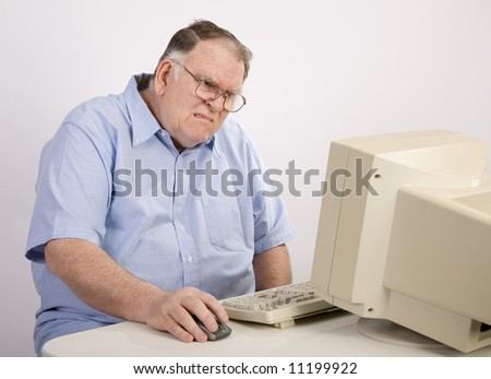 older male working on computer and grimacing