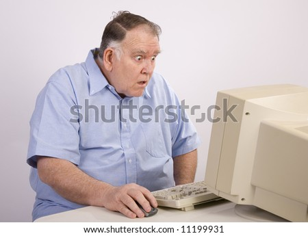 Older man at computer amazed by what he sees