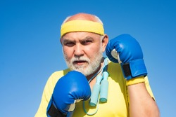 Older man boxing - close up portrait. Handsome elderly man practicing boxing kicks. Senior sport man wearing boxing gloves. Funny bearded man standing in boxing pose. Fighter