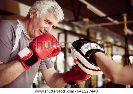 Older man boxing in gym. Senior man with personal trainer.