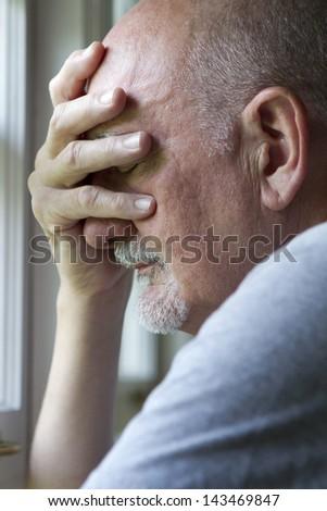 Older man expressing pain or depression.