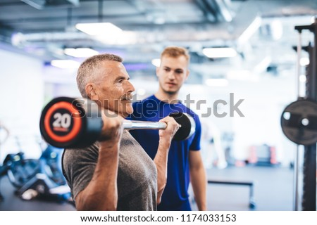 Older man lifting weights, supervised by gym assistant. Sporty lifestyle of elderly people. #1174033153