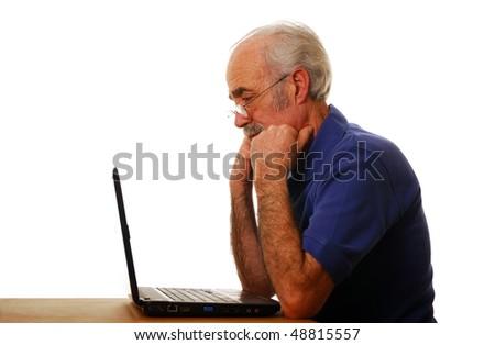 Older man struggling to use laptop