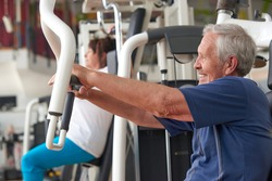 Older man training on press machine at gym club. Aged man training chest muscles using exercise machine at gym. Healthy brain, healthy body.