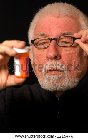 Older man tries to read pill bottle