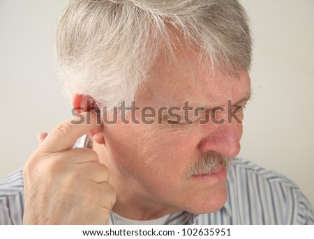 older man tries to relieve the pain deep in his ear